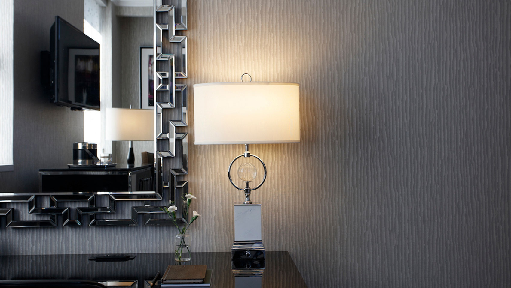 Kimpton Muse Hotel guestroom desk with lamp and mirror on the wall