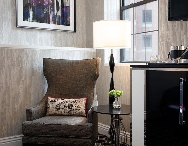 Kimpton Muse Hotel guest room seating area with accent pillow
