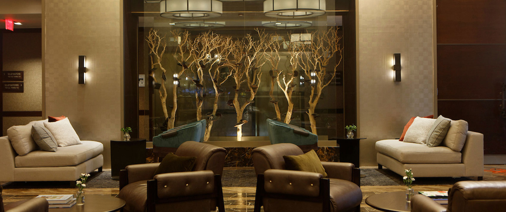 Kimpton Muse Hotel lobby seating area with Autumn tree fixtures in display case